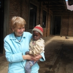 Betty with a baby from an orphanage run by the Consolata Sisters. Betty helped with fundraising efforts.