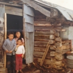 Children standing in entry to their log home in Sleetmute, Alaska.