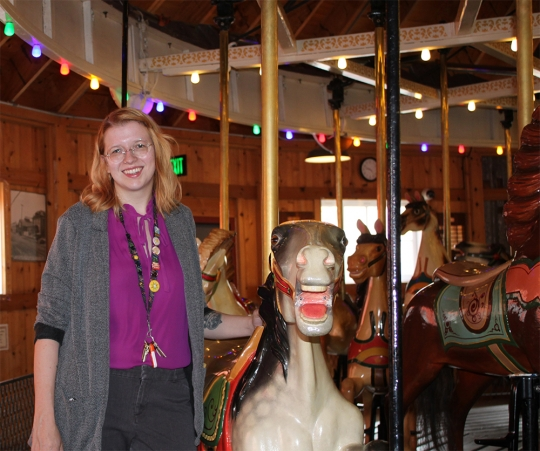 Megan Hahin, '11, executive director of the Herschell Carrousel Factory Museum in North Tonawanda, N.Y., stands near the museum's 1916 carousel, which has 36 hand-carved horses (some of which are from the late 1890s) and more than 580 lights.