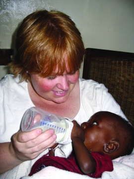 "Adrienne Stanfill spent nearly three weeks in Malawi on a grant-funded mission to assist Malawi Children's Village and Orphan Support Africa. She provided both technical support and direct service to the village's children, including 7-month-old ""Blessings,"" who drank from his first bottle in Adrienne's arms."