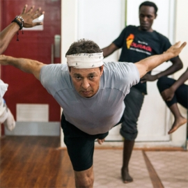John Minerva, '78, (right) in airplane pose at the Africa Yoga Project's teacher training course, held in April 2013 in Nairobi, Kenya. To his right is Dou Dou, a Congolese teacher in training.