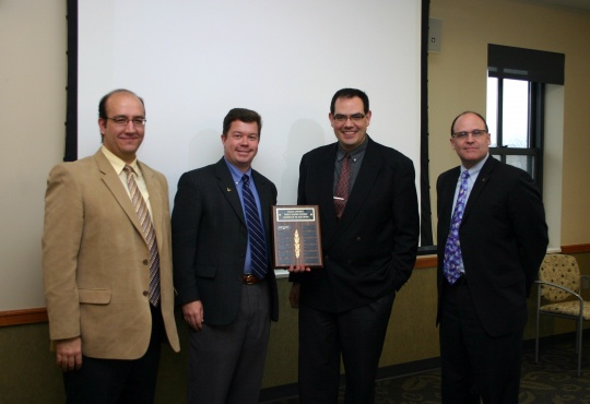 Drs. Mustafa Gokcek and Thomas Chambers of NU's history department accept the award for Student Learning Outcomes Assessment of the Year from Dr. Ronny Priefer, committee chair, and Dr. Timothy Downs, vice president for academic affairs.