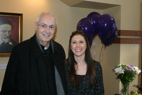 The Rev. Joseph L. Levesque, president, congratulates Sara Villnave on being named Niagara University's Outstanding Employee of the Quarter.