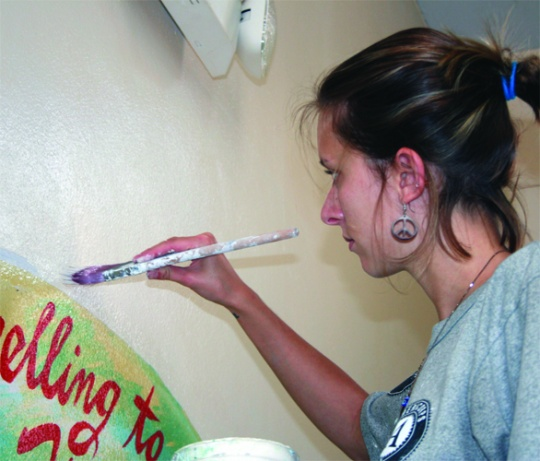 Lacey Howcroft, '09, paint a wall in an elementary school in New Orleans.