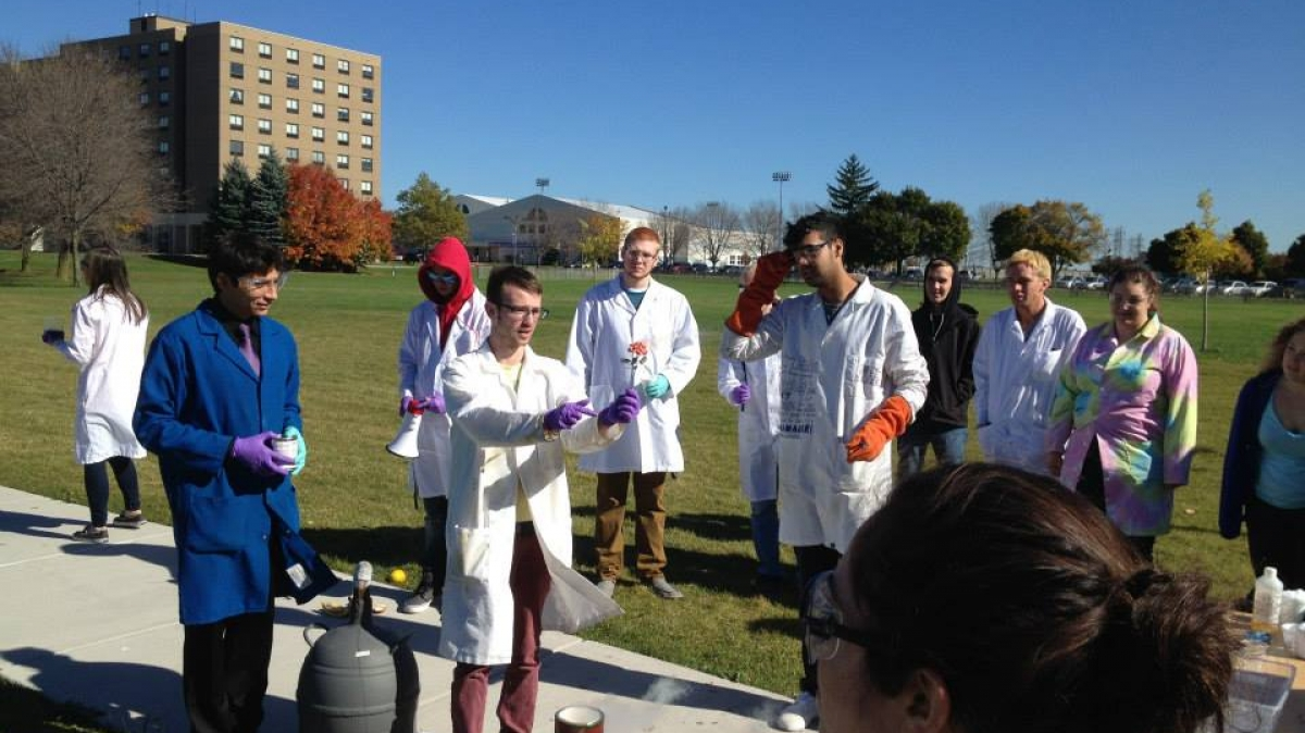 Dr. Sanchez (in blue lab coat) and chemistry students demonstrate an experiment.
